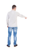 Back view of pointing young men in shirt and jeans. Back view of pointing young man in shirt and jeans, who shows something by his right hand. Young guy gesture Stock Photos