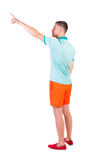 Back view of  pointing young men in  t-shirt and shorts. Royalty Free Stock Images