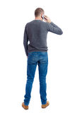 Back view of  pointing young men talking on cell phone. Royalty Free Stock Image