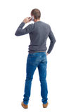 Back view of  pointing young men talking on cell phone. Royalty Free Stock Photography