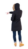 Back view of  pointing young woman in parka. Young girl gestures. girl shows something to the left by her right hand. Rear view people collection.  backside Stock Photos