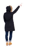 Back view of  pointing young women in parka. Stock Photos