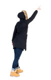 Back view of  pointing young women in parka. Stock Photo