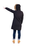 Back view of  pointing young women in parka. Back view of  pointing young woman in parka. Young girl gestures. She shows us something at the left corner of Stock Photos