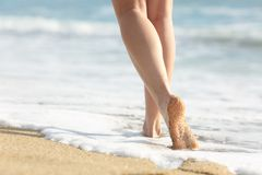 Girl legs walks on the sand and sea water on the beach. Back view portrait of a beautiful girl legs walks on the sand and sea water on the beach royalty free stock photos
