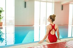 Young Woman Sitting in Swimming Pool. Back view portrait of beautiful young woman sitting at pool border with legs in water, looking away gracefully, copy space stock photo