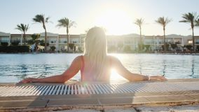 Back view portrait of blonde young girl, looking at sunset. Woman in red swimsuit sitting in a blue water pool. Bikini stock footage