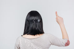 Back view portrait of a brunete girl pointing finger up Stock Photos