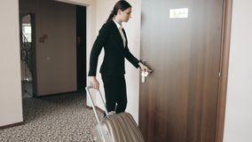 Back view portrait of a business woman in skirt suit on high heels walking with her suitcase along hotel lobby