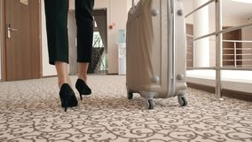 Back view portrait of a business woman in skirt suit on high heels walking with her suitcase along hotel lobby. Back view portrait of a business woman skirt stock video