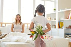 Girl Surprising Mom with Flowers stock photos