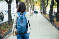 Back view portrait of a female student walking. In the city park outdoors Stock Images