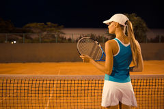 Back view portrait of a female tennis player. With racket at court royalty free stock photo