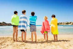 Friends wrapped in beach towels admiring seascape royalty free stock photography