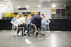 Support Group Meeting. Back view portrait of handicapped men sharing troubles with support group during therapy session, copy space royalty free stock photography