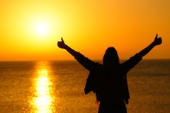 Happy woman with thumbs up celebrating sunrise stock photography
