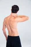 Back view portrait of a man having neck pain Stock Photos