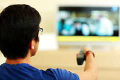 Back view portrait of a man watching tv. At home in the living room Royalty Free Stock Image