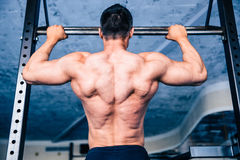 Back view portrait of a muscular man pulling up. At gym Royalty Free Stock Image