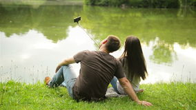 Back view portrait of a romantic couple sitting on the green grass near the lake and taking photo by selfie stick. stock video footage