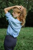 Back view portrait of sexy blonde girl with curly hair wearing blue casual jeans blouse posing in the park on green