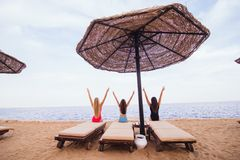 Back view portrait of three sexy women friends sitting and resting in lounge chairs with umbrella on the sea beach. Rear view. Back view portrait of three women Royalty Free Stock Image