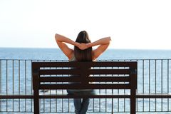 Woman relaxing on the beach sitting on a bench. Back view portrait of a woman relaxing on the beach sitting on a bench contemplating ocean stock photography