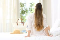 Woman relaxing in an hotel room in summer vacations. Back view portrait of a woman relaxing sitting on a bed of an hotel room looking through a window in summer Stock Photography