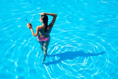 Back view portrait of a woman standing in swim pool Royalty Free Stock Image