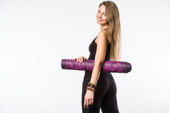 Back view portrait of a young fitness woman with yoga mat over white background Stock Images