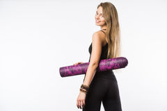 Back view portrait of a young fitness woman with yoga mat over white background Royalty Free Stock Images