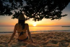 Back view of pregnant woman sit on sand and watching sunset at tropical beach. Woman wear swimsuit and straw hat relaxing stock photography