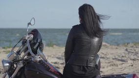 Back view of the pretty caucasian girl sitting on the motorcycle looking away on the riverbank. Hobby, traveling and. Active lifestyle. Leisure and travel by stock video footage
