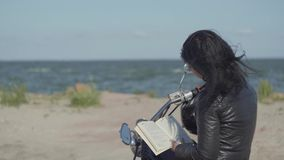 Back view of the pretty caucasian girl in a black leather jacket sitting on the motorcycle reading book. Hobby. Back view of the pretty caucasian girl sitting on stock video footage