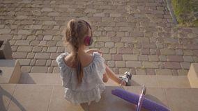 Back view of a pretty cute little girl in headphones reading the book, the small plane lying on the porch. The child. Back view of the pretty cute little girl in stock video footage