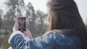 Back view of pretty glamour woman in jeans jacket and glasses taking photo of beautiful nature on her cellphone. Back view of pretty glamour woman in jeans stock footage