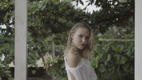 Back view of pretty natural woman on summer day in boho style fashion wearing white shirt, bikini and earrings shaking hair. stock video footage