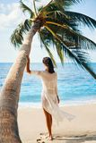 Back view of pretty young woman relax and enjoy sea standing under palm tree on tropical beach stock photo