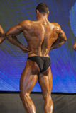 Back View of Professional Male Caucasian Bodybuilder Performing. On Stage. Vertical Image Composition Stock Image