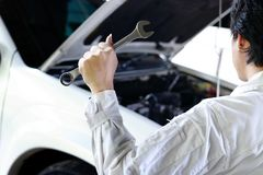 Back view of professional mechanic in uniform with wrench repairing engine under hood of car at  garage. Car insurance concept. Back view of professional Stock Photo