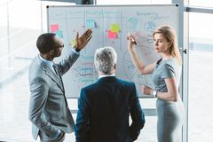 back view of professional multiethnic business people discussing charts and graphs royalty free stock image