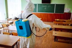 Back view of a professional sanitary worker disinfecting the classroom before the academic year starts. A man wearing protective