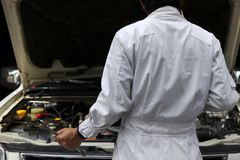 Back view of professional young mechanic man in white uniform with wrench diagnosing engine against car in open hood at the repair. Garage Stock Image