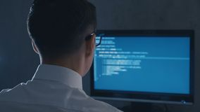 Back view of programmer professional in glasses programming code on computer monitor at night office stock video footage