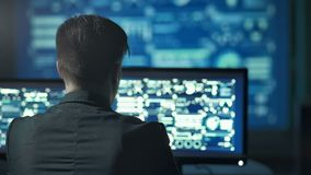 Back view of programmer working on computer in dark digital office.  stock footage