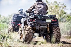 Back view of quad bike  riding along a country road. Royalty Free Stock Images