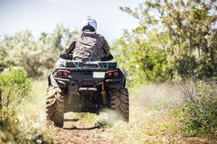 Back view of quad bike  riding along a country road. Royalty Free Stock Photo
