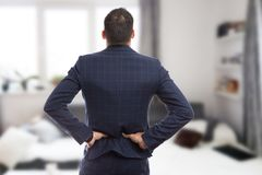 Back view of realtor suffering lumbar pain. As spine injury and health insurance concept Stock Images