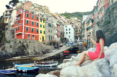 Back view of red dressed girl sitting on the stones like a mermaid taking photo with mirrorless camera of Italian Riviera landscap Royalty Free Stock Images