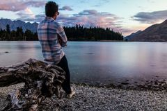 Man leaning on driftwood and admiring nature royalty free stock photo